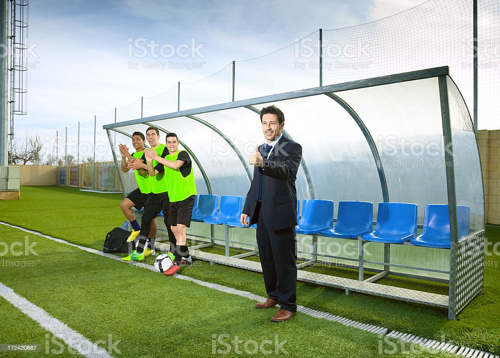 Soccer coach and reserve players cheering stock photo