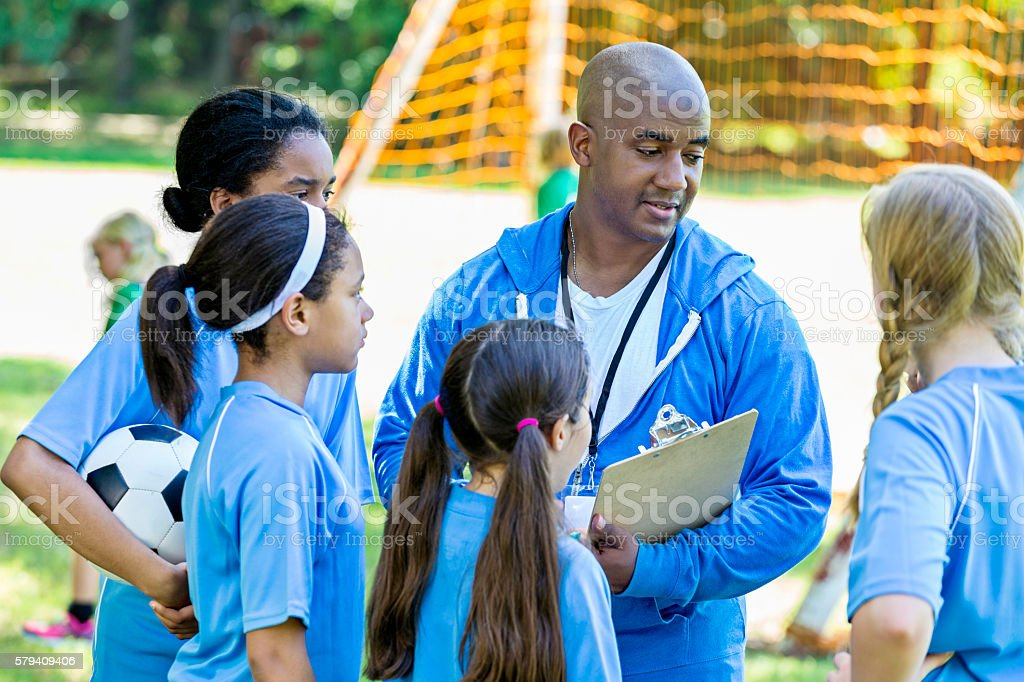 Soccer coach discussing plays with his girls soccer team stock photo