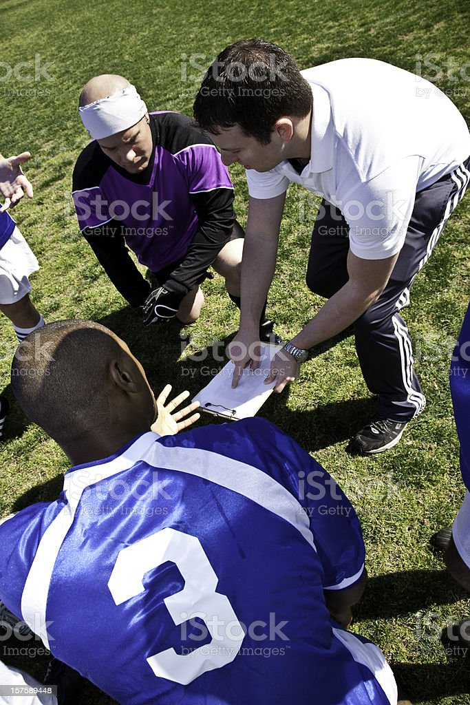 Soccer Coach Explaining Strategy to Team During Time Out stock photo