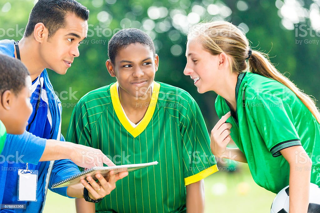 Soccer coach gives instructions to female teenage player stock photo