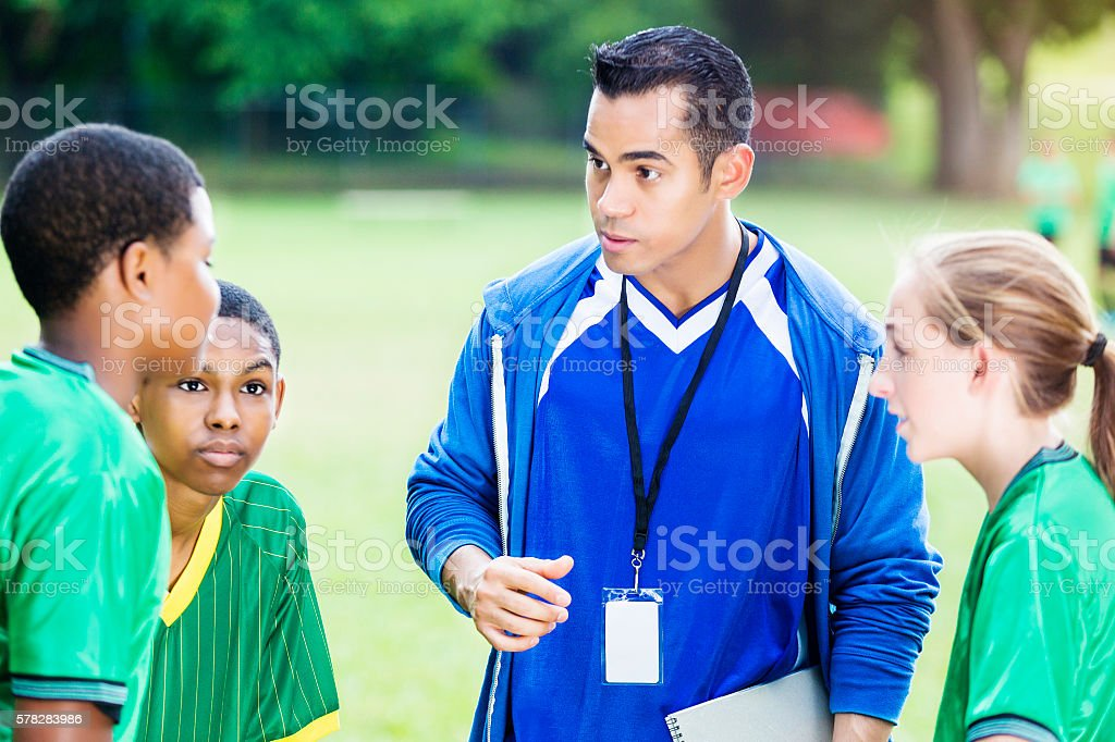 Soccer coach gives players pep talk stock photo