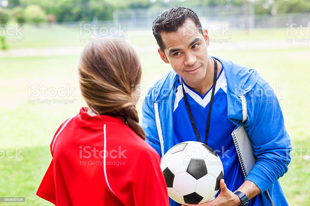 Soccer coach hands player the ball stock photo