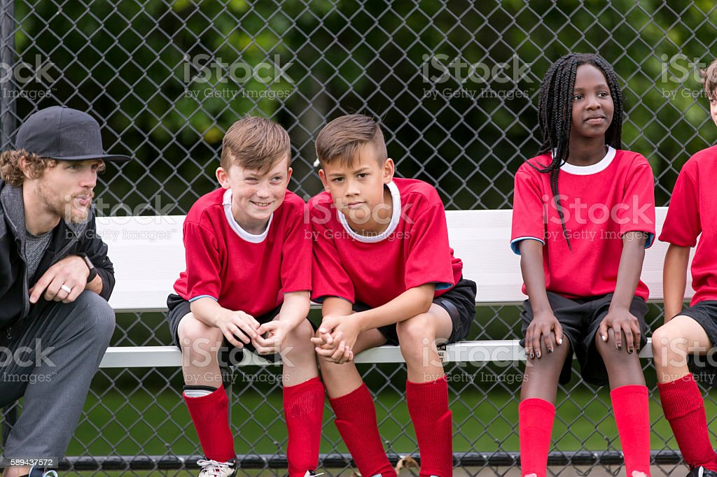 Soccer coach with his diverse childrens soccer team stock photo