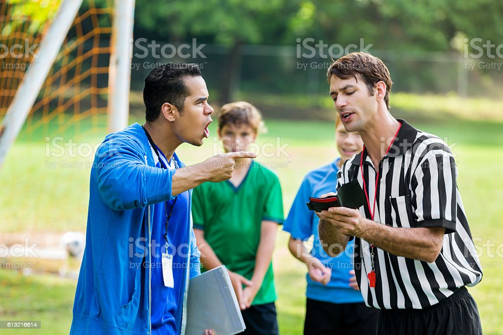 Soccer coach yells at referee over bad call stock photo