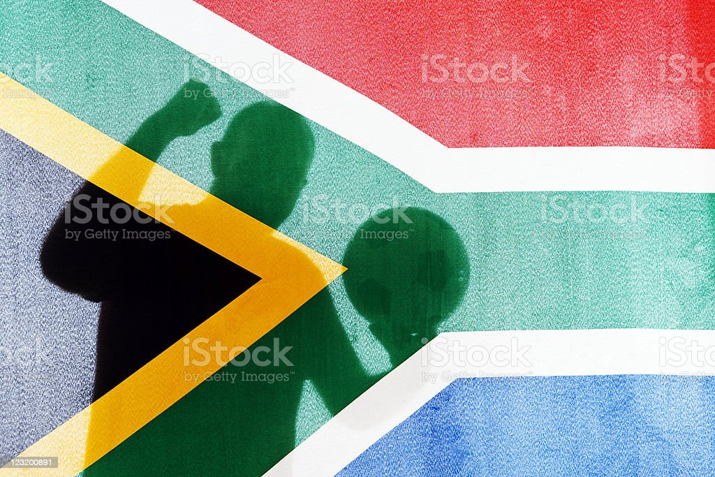 SA soccer fan holding ball seen through South African flag royalty-free stock photo