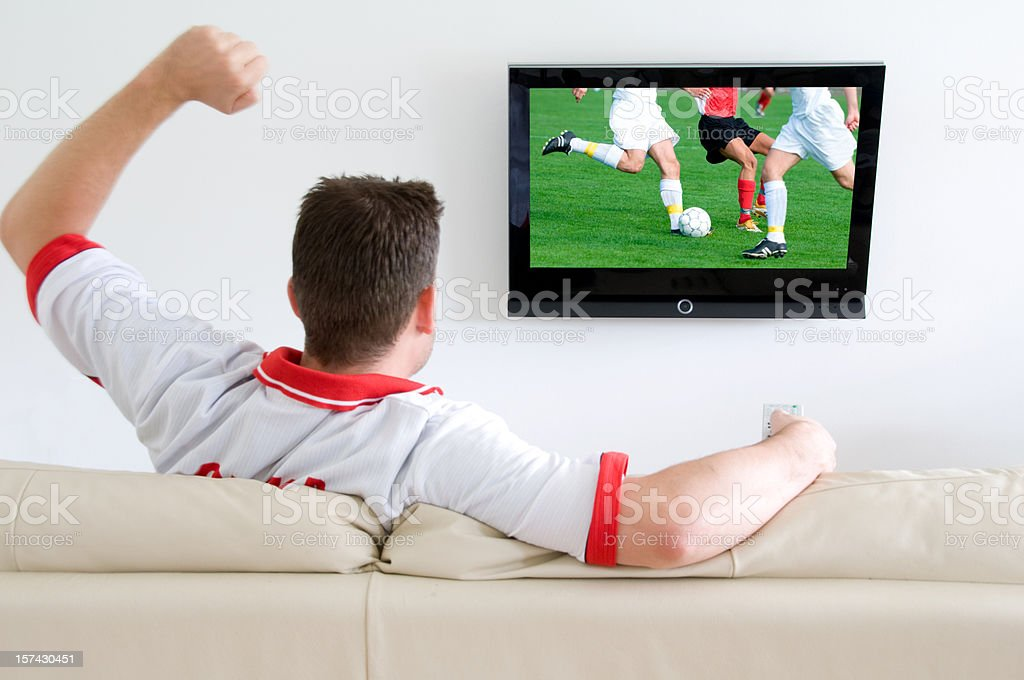 Soccer fan watches a football match on tv and cheers royalty-free stock photo
