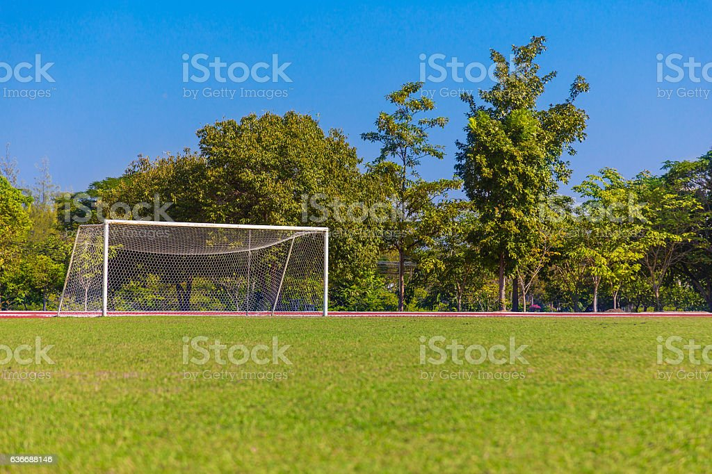 soccer field and white goal with trees and blue sky background stock photo