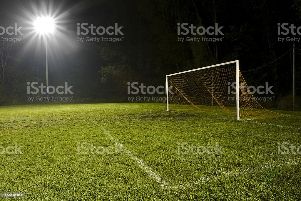 A soccer field at night lit up by a floodlight royalty-free stock photo