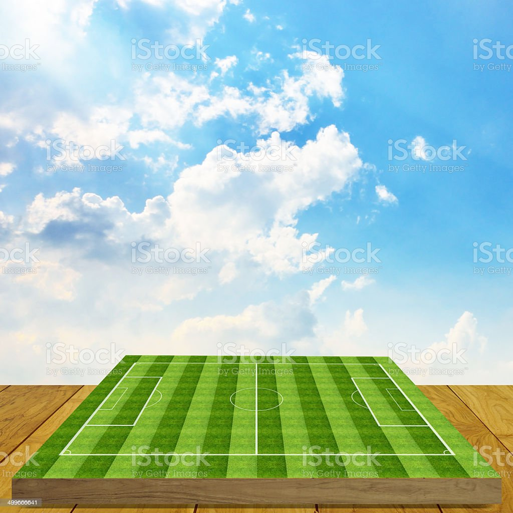 Soccer field board game on wooden floor with nice sky stock photo
