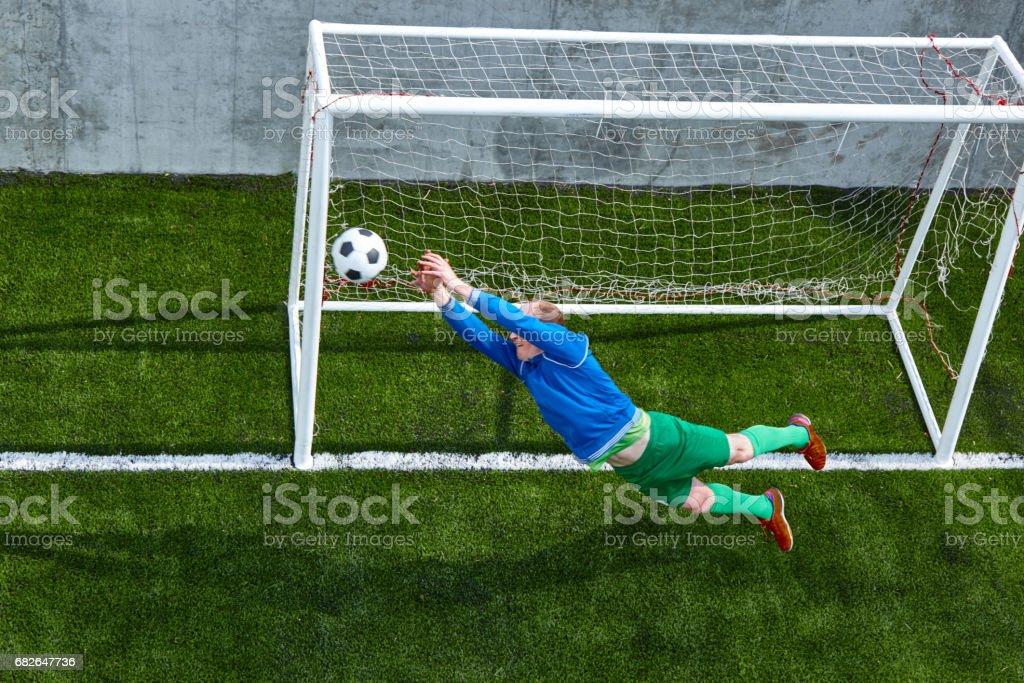 Soccer football goalkeeper making diving save stock photo