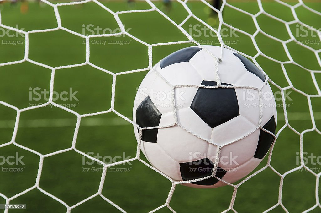 Soccer football in Goal net with green grass field. royalty-free stock photo