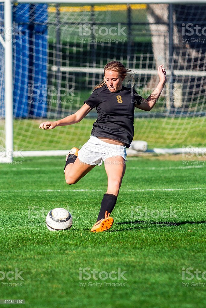 Soccer Girl in Black Jersey on Flying Kick Approach stock photo
