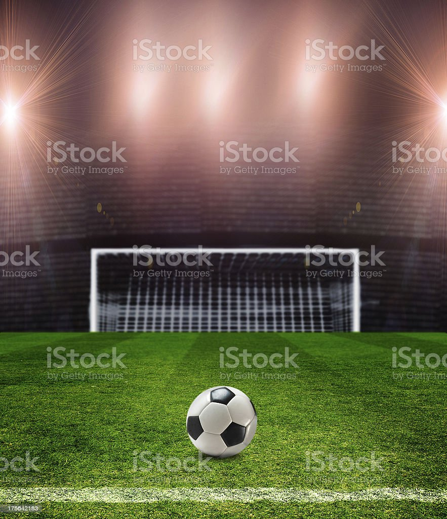 A soccer goal and ball under the stadium lights royalty-free stock photo