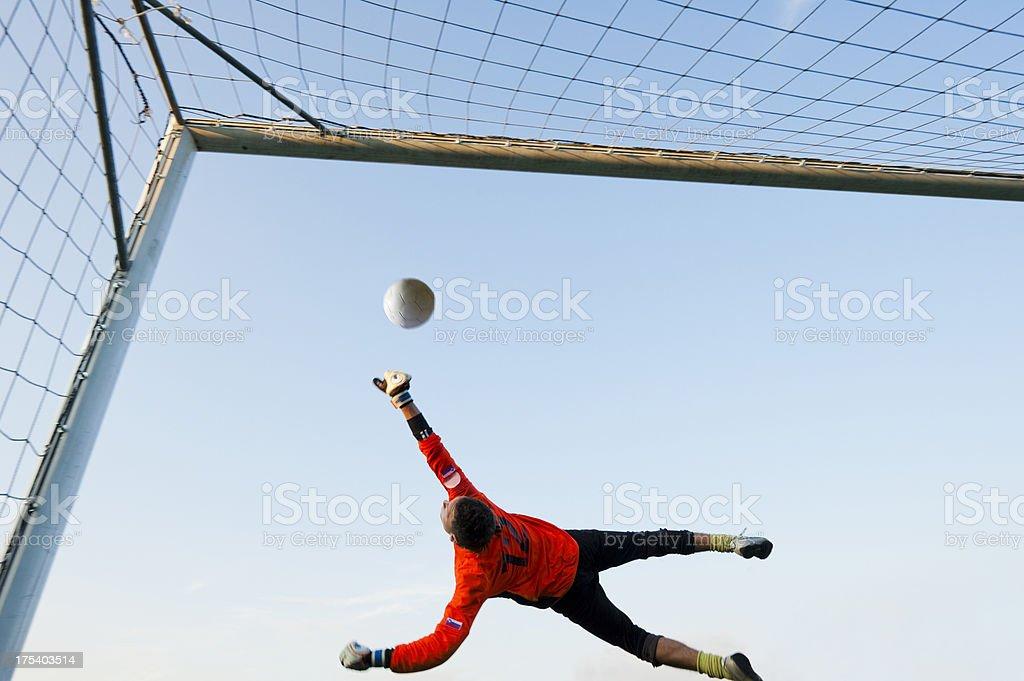 Soccer goalie defending in mid-air stock photo