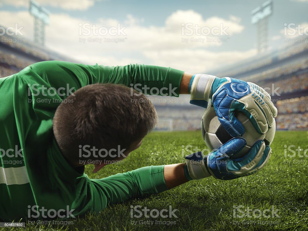 Soccer goalkeeper catches a ball stock photo