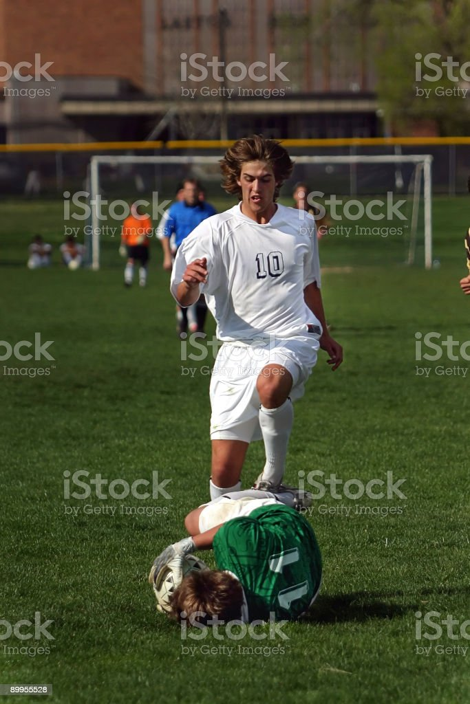 Soccer Male Goalkeeper in Green Captures Ball Underfoot of Striker stock photo