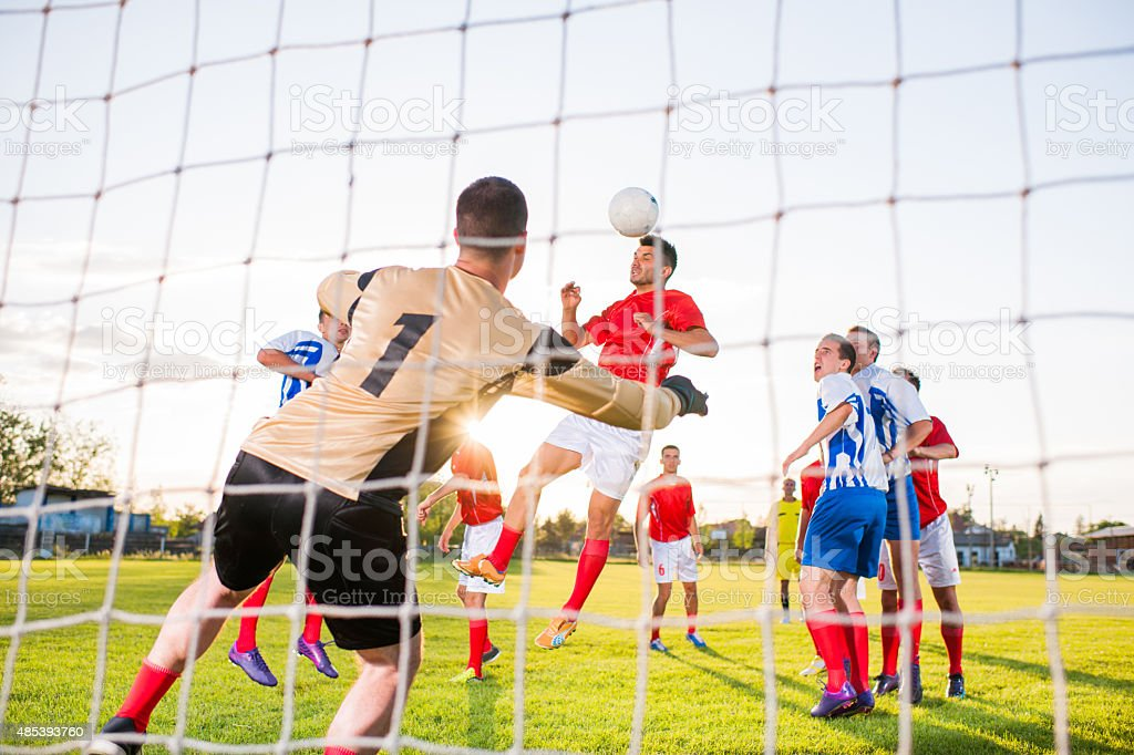 Soccer match from the goalkeeper's net. stock photo