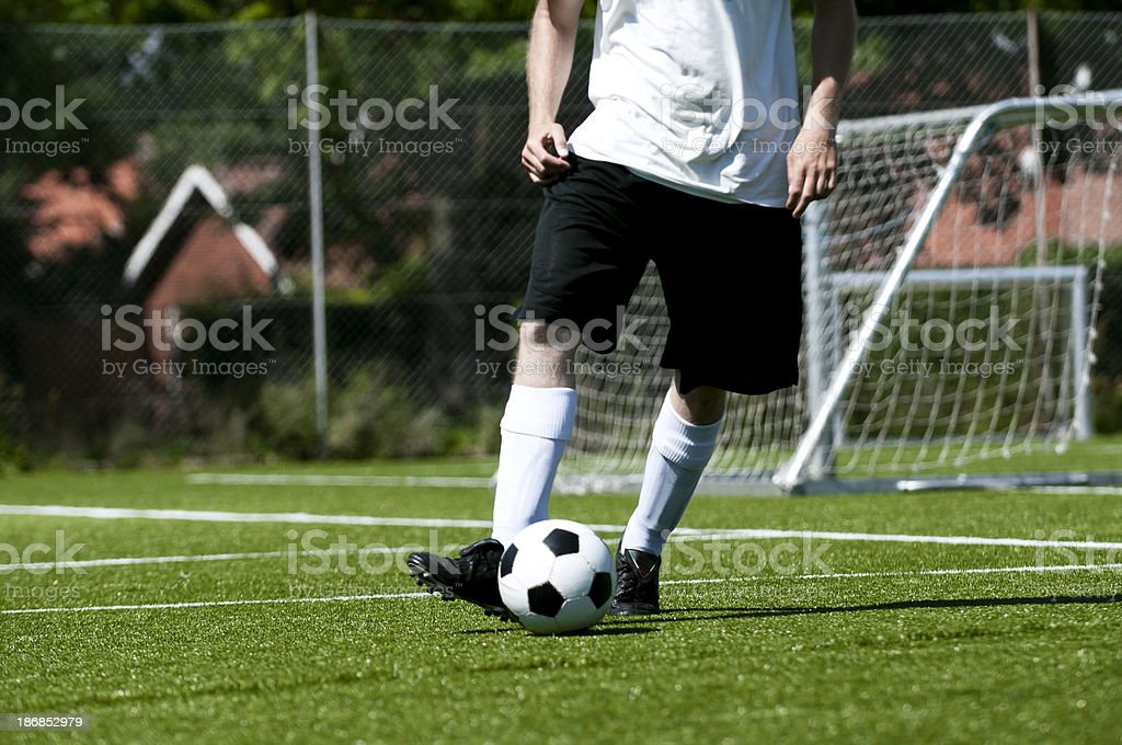 Soccer player and ball on the pitch royalty-free stock photo