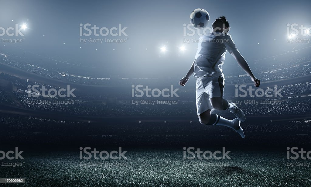 A soccer player at a stadium mid air kicking a ball stock photo