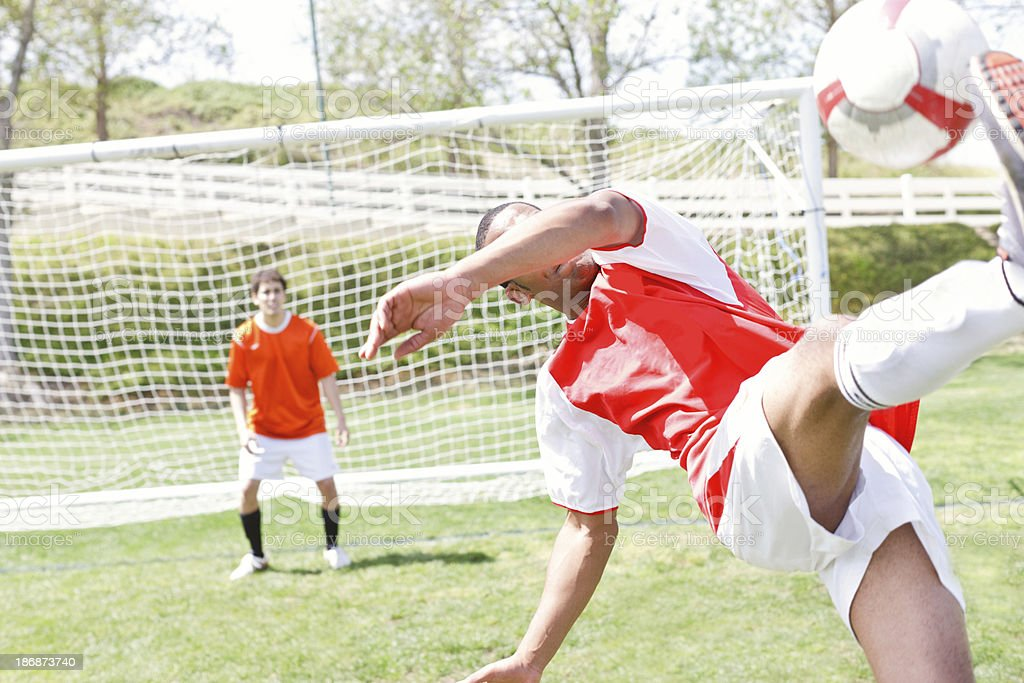 Soccer player doing a scissor kicking ball into goal royalty-free stock photo