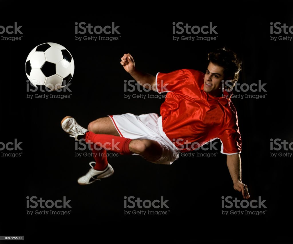 Soccer Player Doing Flying Kick with Ball, Isolated on Black royalty-free stock photo