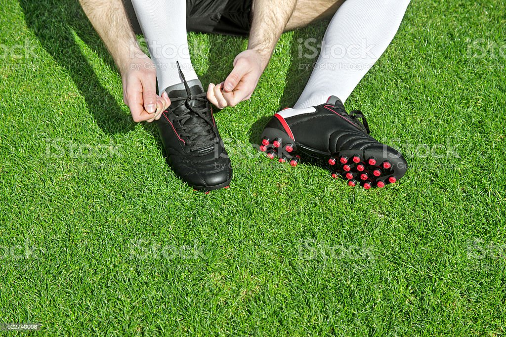 Soccer player fixing his soccer shoes stock photo