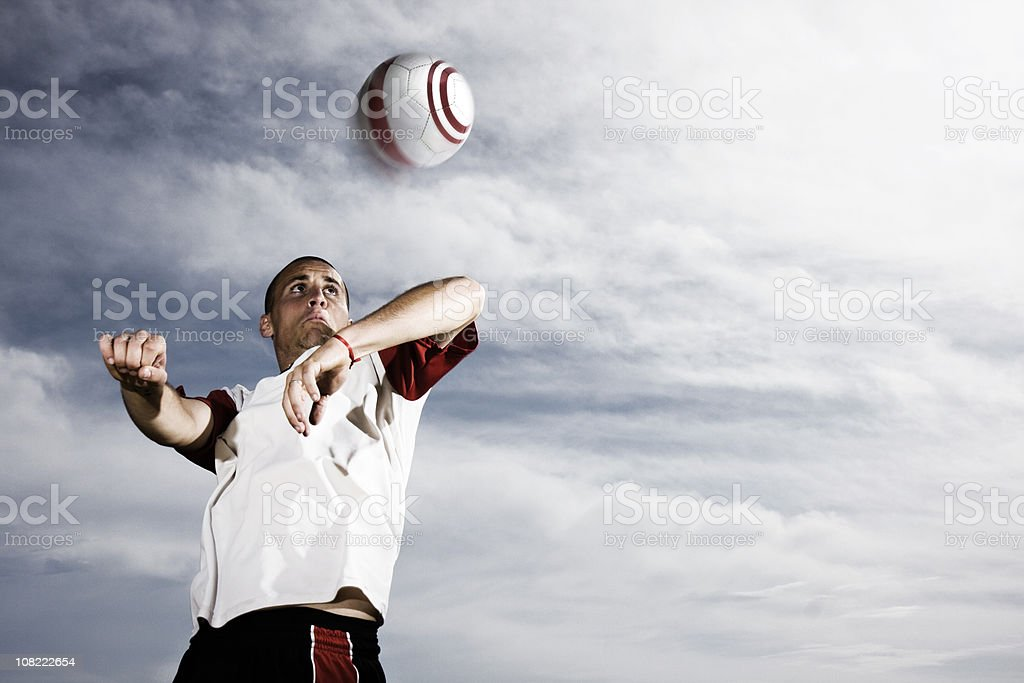 Soccer Player Heading Ball Against Stormy Sky stock photo