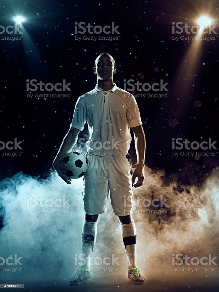 Soccer player holding a ball amidst smoke and spotlights stock photo