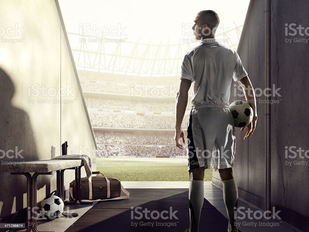 Soccer player holding ball getting ready to enter the field stock photo