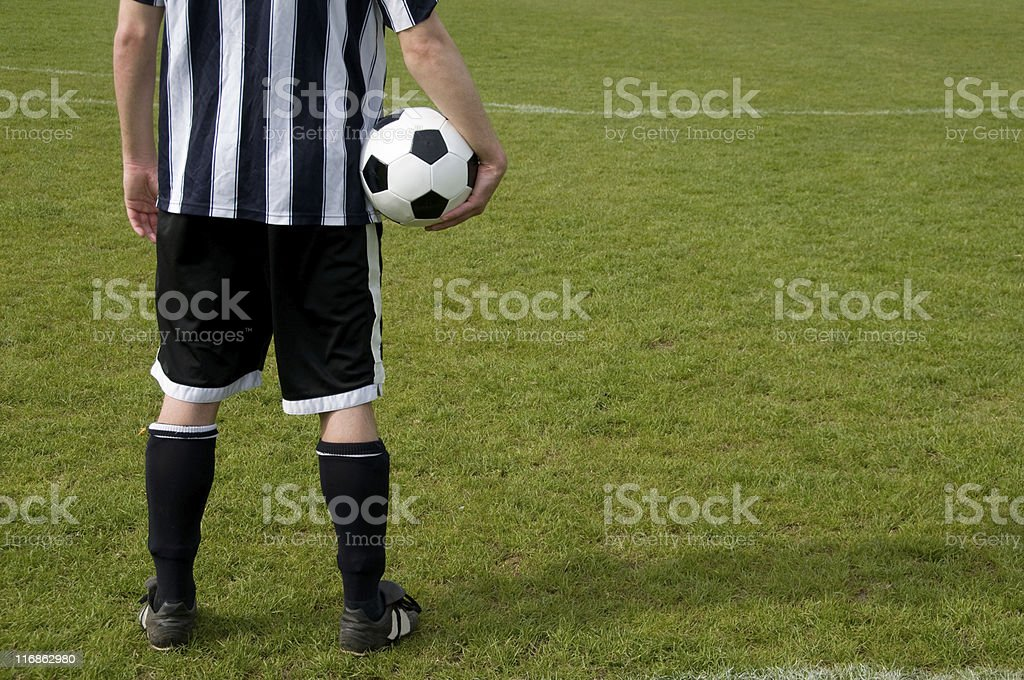Soccer player holds ball and waits for the next game royalty-free stock photo