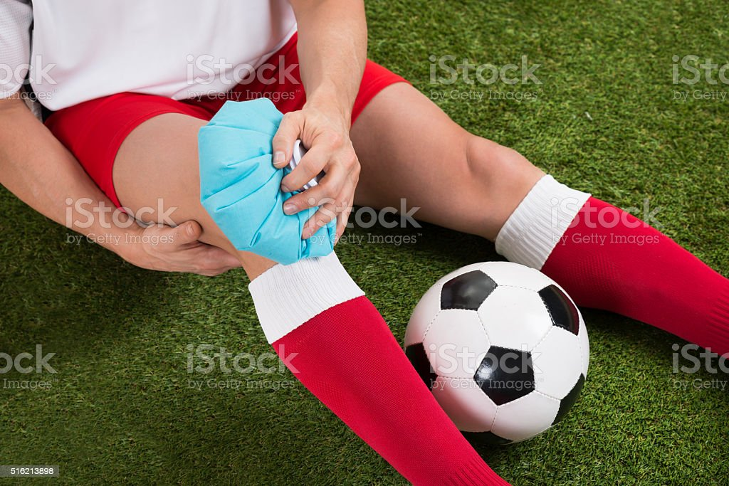 Soccer Player Icing Knee With Ice Pack stock photo