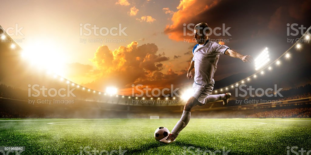 Soccer player in action on sunset stadium panorama background stock photo