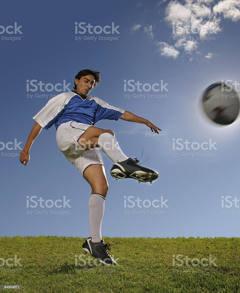 Soccer player in blue jersey hitting the ball royalty-free stock photo