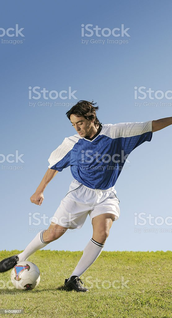 Soccer player in blue jersey playing with ball stock photo
