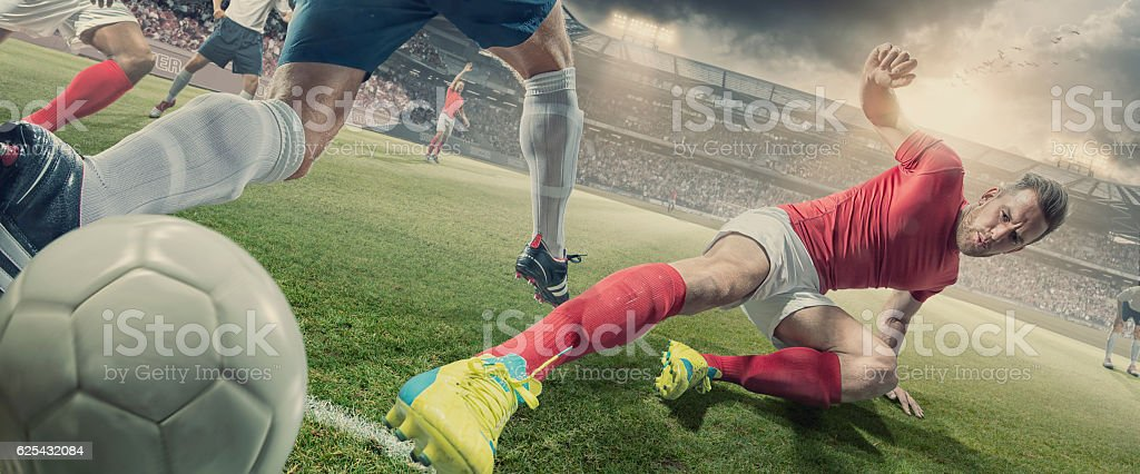 Soccer Player in Sliding Tackle During Football Match In Stadium stock photo