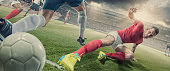 Soccer Player in Sliding Tackle During Football Match In Stadium