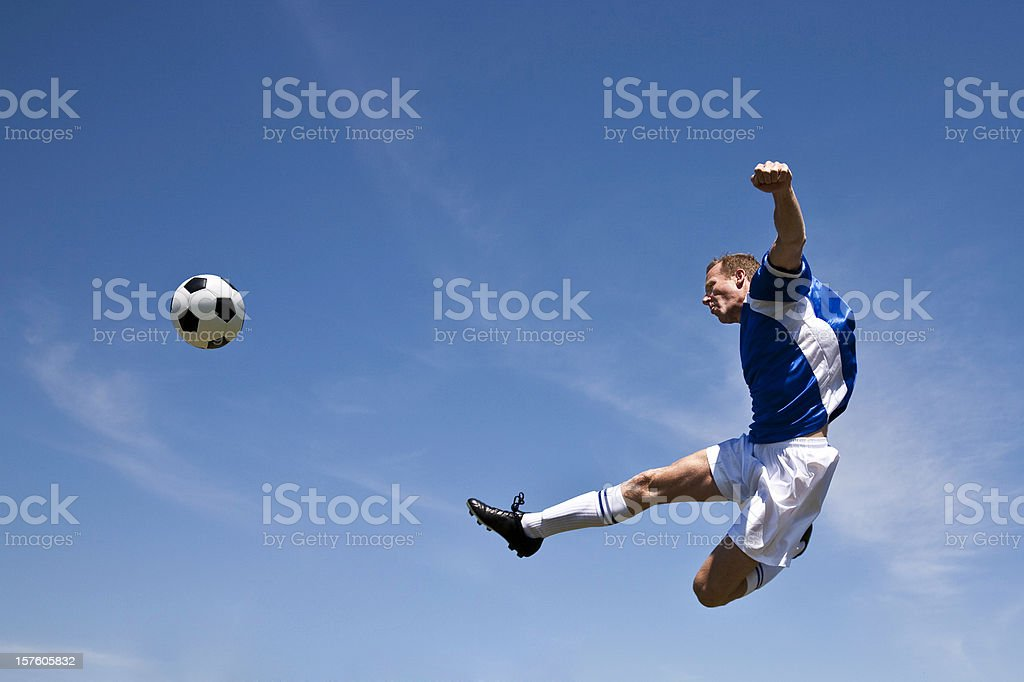 Soccer Player in the Air Kicking Ball royalty-free stock photo