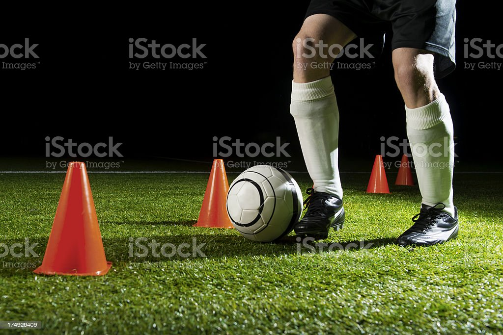 Soccer player is practicing with ball and cones at night royalty-free stock photo