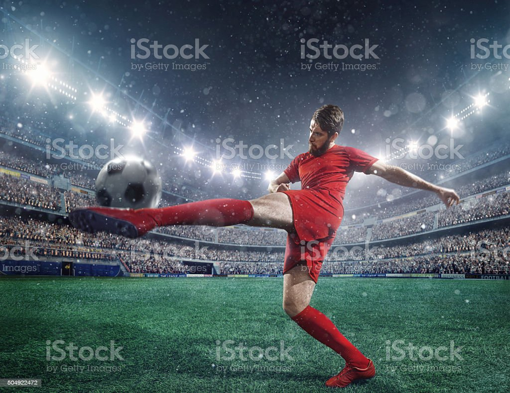 Soccer player kicking a ball stock photo