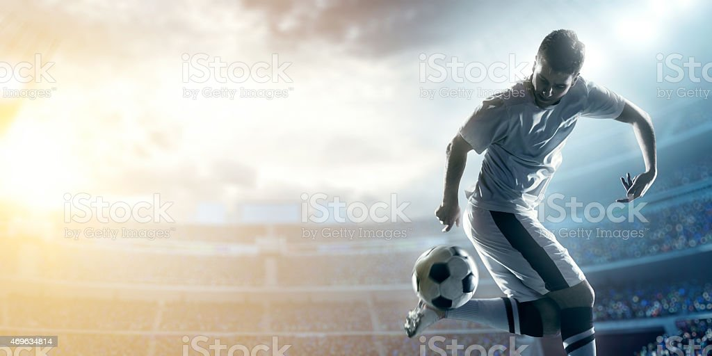 Soccer player kicking ball behind his back in the stadium  stock photo
