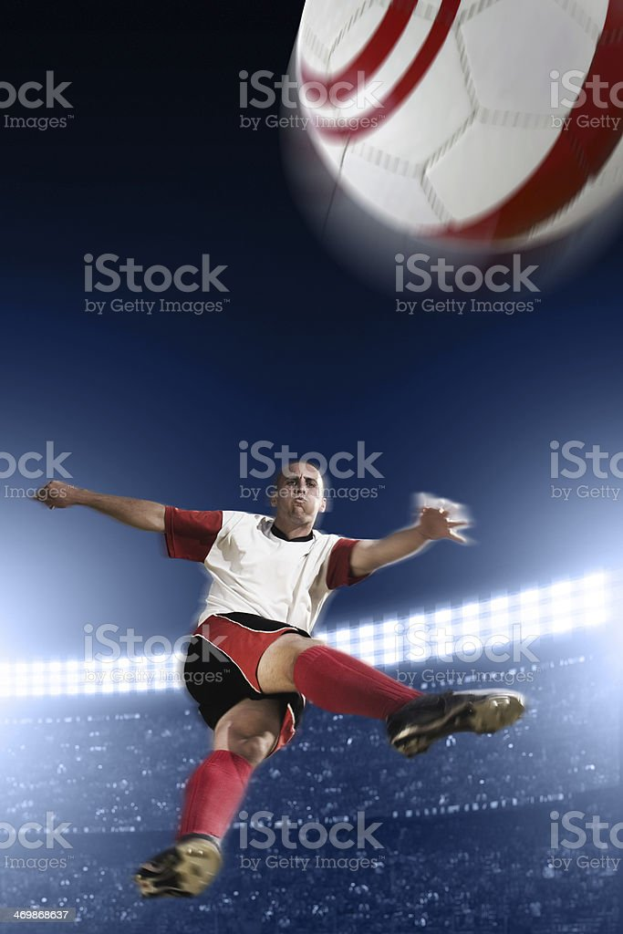 Soccer Player Kicking Ball in Mid Air stock photo