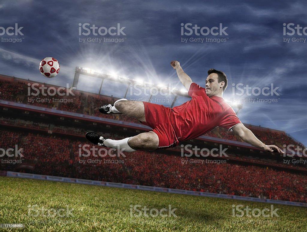 Soccer player kicking ball in midair royalty-free stock photo