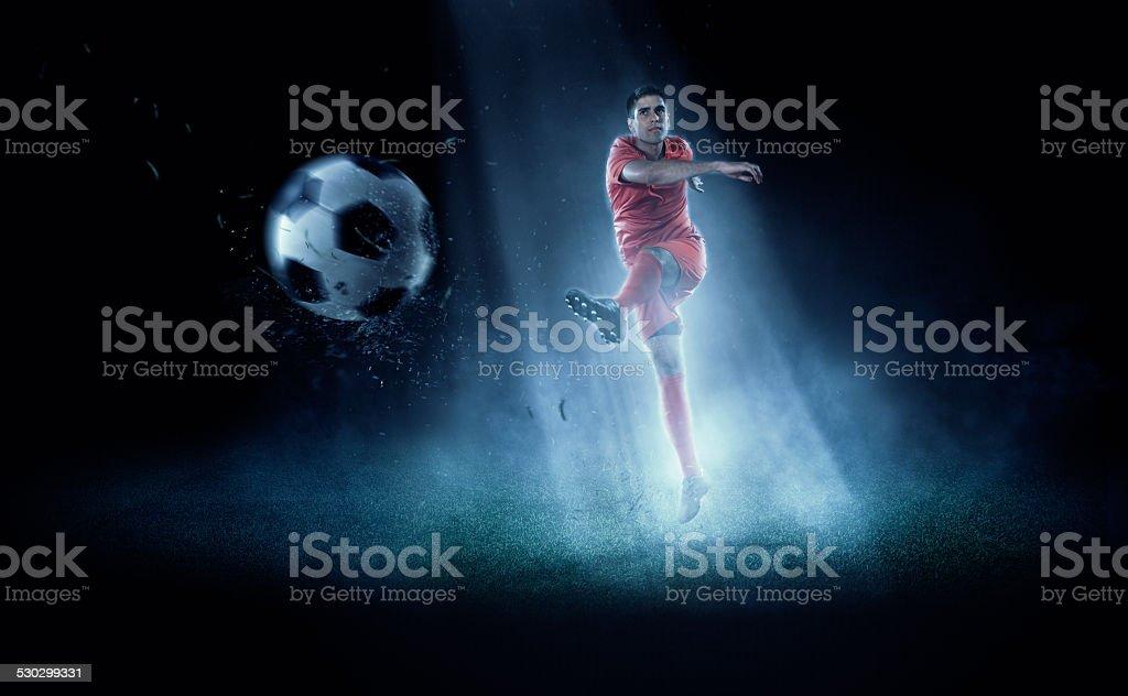 Soccer player kicking ball in spotlight stock photo