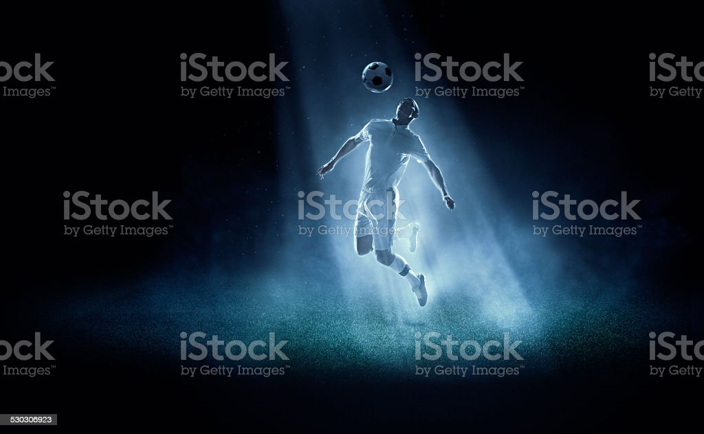 Soccer player kicking ball in spotlight stock photo