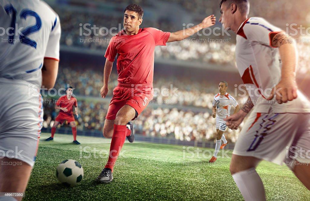 Soccer player kicking ball in stadium stock photo