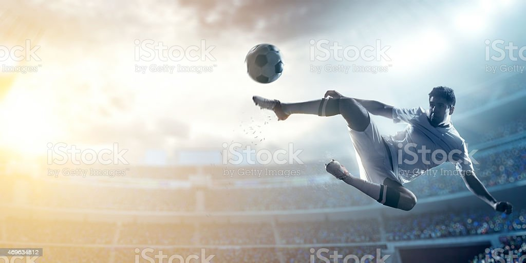 A male soccer player makes a dramatic play by jumping horizontally....