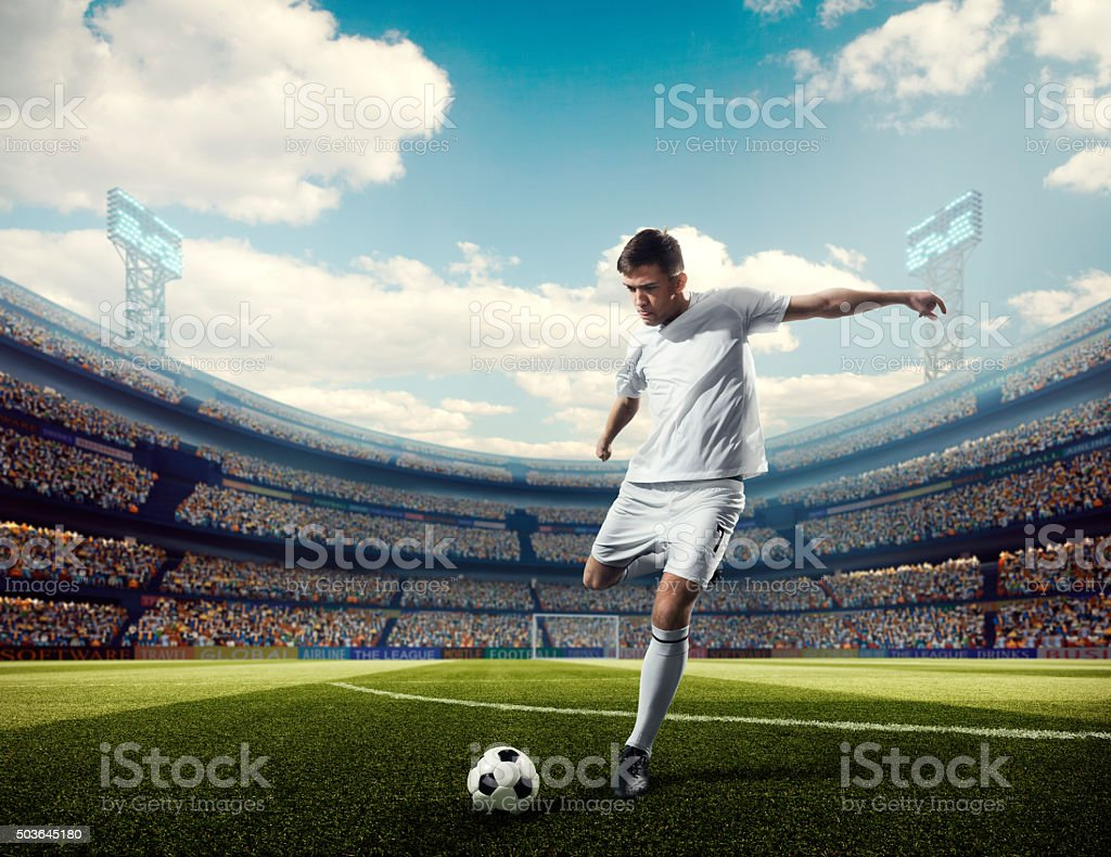 Soccer player kicking ball in stadium stock photo