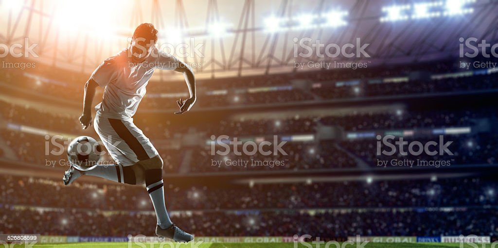 Soccer Player Kicking Ball on stadium stock photo