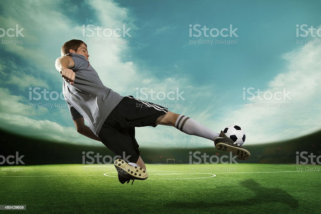 Soccer player kicking the ball in mid air stock photo