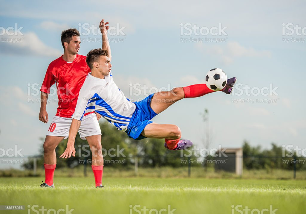 Soccer player kicking the ball while being in mid air. stock photo
